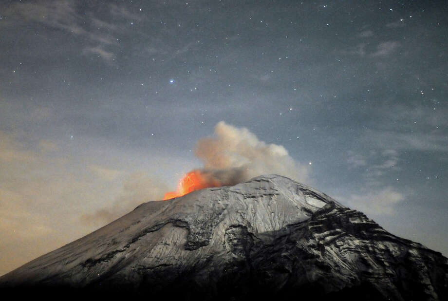 "A cloud of ash belches out of Mexico's Popocatepetl volcano, some near Mexico City, as seen from Paso de Cortes, in the Mexican central state of Puebla. Authorities have raised the alert level to ""Yellow Phase Three,"" the fifth of a seven-stage warning system, restricting access to an area of 12 km around the volcano while preparing evacuation routes and shelters. Photo: AFP, AFP/Getty Images / 2013 AFP"
