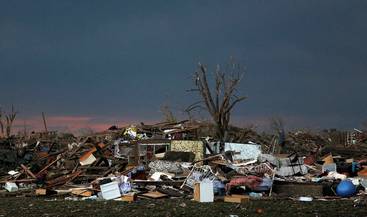 The rubble of a destroyed neighborhood lay mixed together where it fell Tuesday, May 21, 2013 a day after a tornado moved through Moore, Okla. The huge tornado roared through the Oklahoma City suburb Monday, flattening entire neighborhoods and destroying an elementary school with a direct blow as children and teachers huddled against winds.