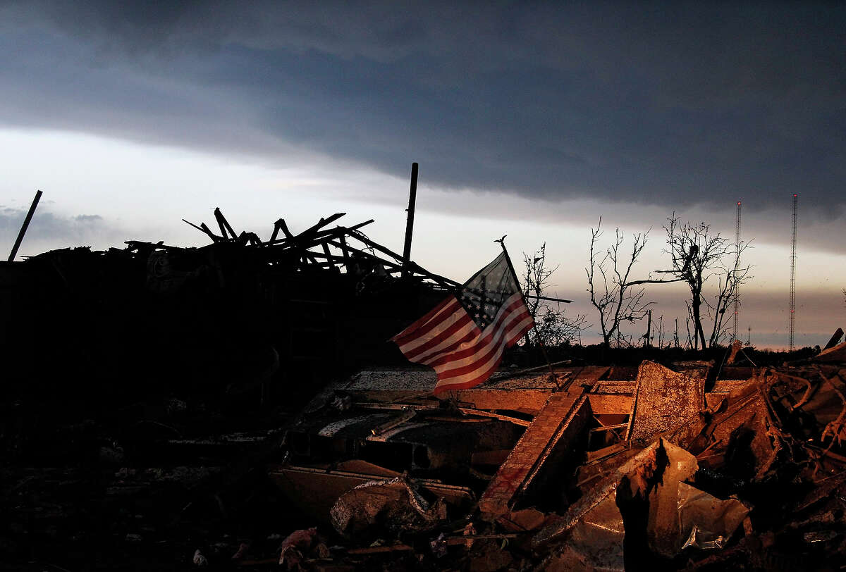 At sunrise Tuesday May 21, 2013, an American flag blows in the wind atop the rubble of a destroyed home in Moore, Okla., A huge tornado roared through the Oklahoma City suburb Monday, flattening entire neighborhoods and destroying an elementary school.
