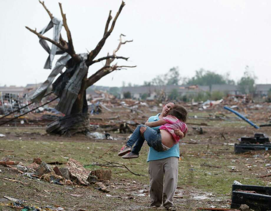 A woman carries her child through a field near the collapsed Plaza Towers Elementary School in Moore, Okla., Monday, May 20, 2013. A tornado as much as a mile wide with winds up to 200 mph roared through the Oklahoma City suburbs Monday, flattening entire neighborhoods, setting buildings on fire and landing a direct blow on an elementary school.  Photo: Sue Ogrocki, Associated Press / AP