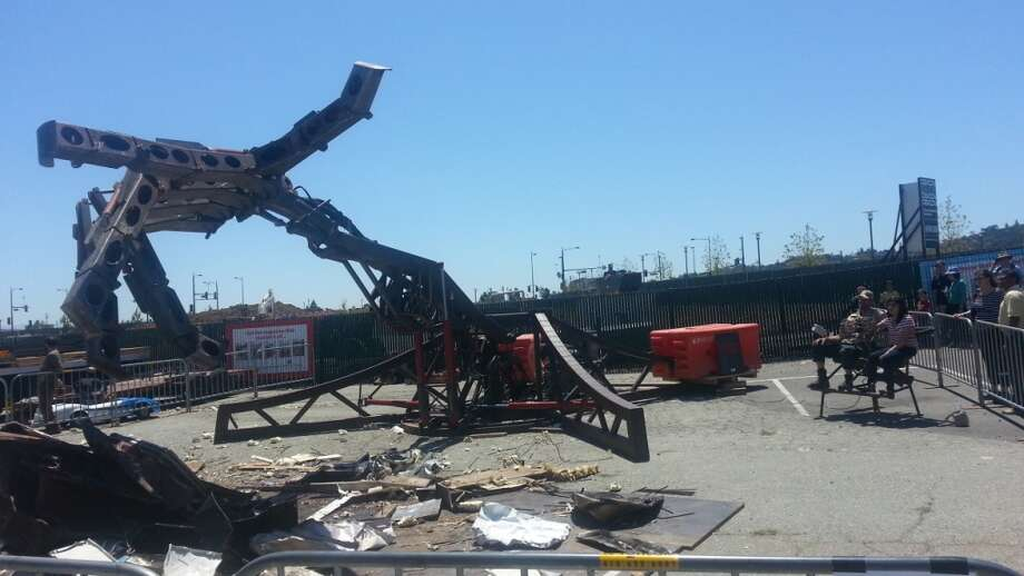 A giant metal hand picks up scrap metal and crushes it. The movements are controlled by a metal glove.