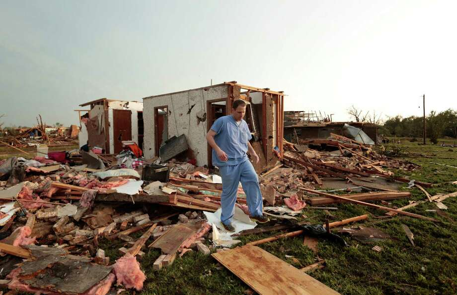 Nathan Ulepich searches outside the back of his house destroyed after a powerful tornado ripped through the area on May 20, 2013 in Moore, Oklahoma. The tornado, reported to be at least EF4 strength and two miles wide, touched down in the Oklahoma City area on Monday killing at least 51 people. Photo: Brett Deering, Getty Images / 2013 Getty Images