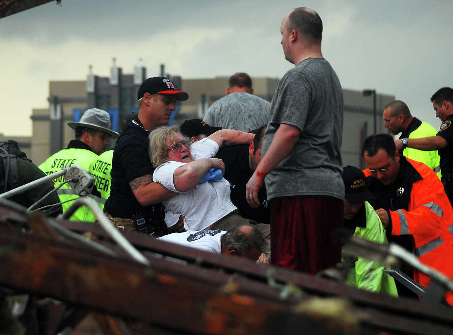 Emergency workers pull out a woman that was trapped in a building that was destroyed off of 4th Street and Interstate 35 after a tornado ripped through Moore, Okla.,  Monday May 20, 2013. Photo: Kyle Phillips, ASSOCIATED PRESS / AP2013