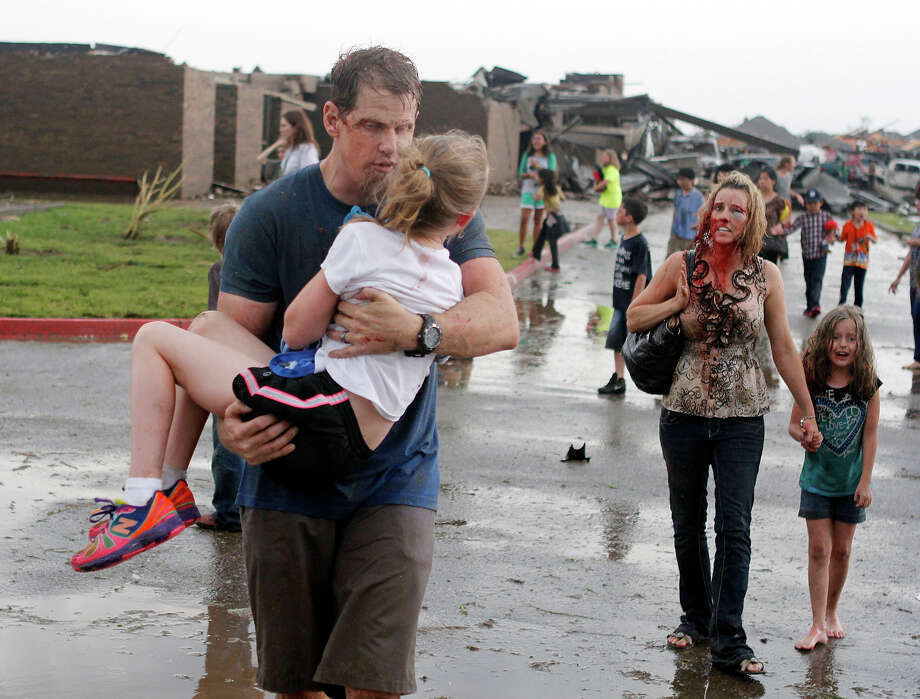 Teachers carry children away from Briarwood Elementary school after a tornado destroyed the school in south Oklahoma City, Monday, May 20, 2013. A monstrous tornado roared through the Oklahoma City suburbs, flattening entire neighborhoods with winds up to 200 mph, setting buildings on fire and landing a direct blow on an elementary school. Photo: Paul Hellstern, AP / The Oklahoman