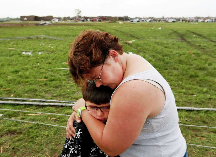 Rebekah Stuck hugs her son, Aiden Stuck, 7, after she found him in front of the destroyed Briarwood Elementary after a tornado struck south Oklahoma City and Moore, Okla., Monday, May 20, 2013. Aiden Stuck was inside the school when it was hit. Photo: NATE BILLINGS, Associated Press / The Oklahoman
