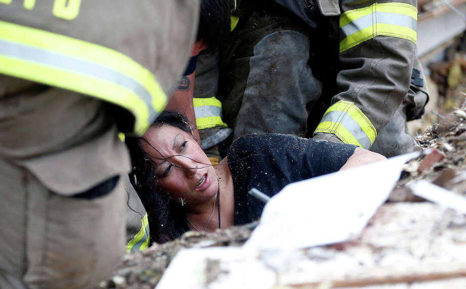 A woman is pulled out from under tornado debris at the Plaza Towers School in Moore, Okla., Monday, May 20, 2013. A tornado as much as a mile wide with winds up to 200 mph roared through the Oklahoma City suburbs Monday, flattening entire neighborhoods, setting buildings on fire and landing a direct blow on an elementary school. Photo: Sue Ogrocki, ASSOCIATED PRESS / AP2013