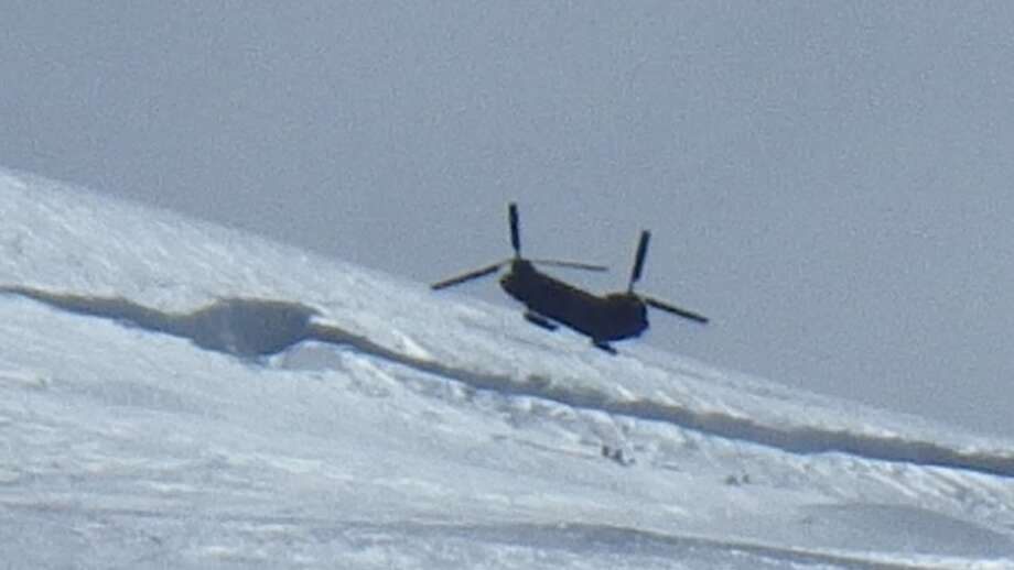 Army Chinook over the top of four Texans being rescued on Mount Rainier
