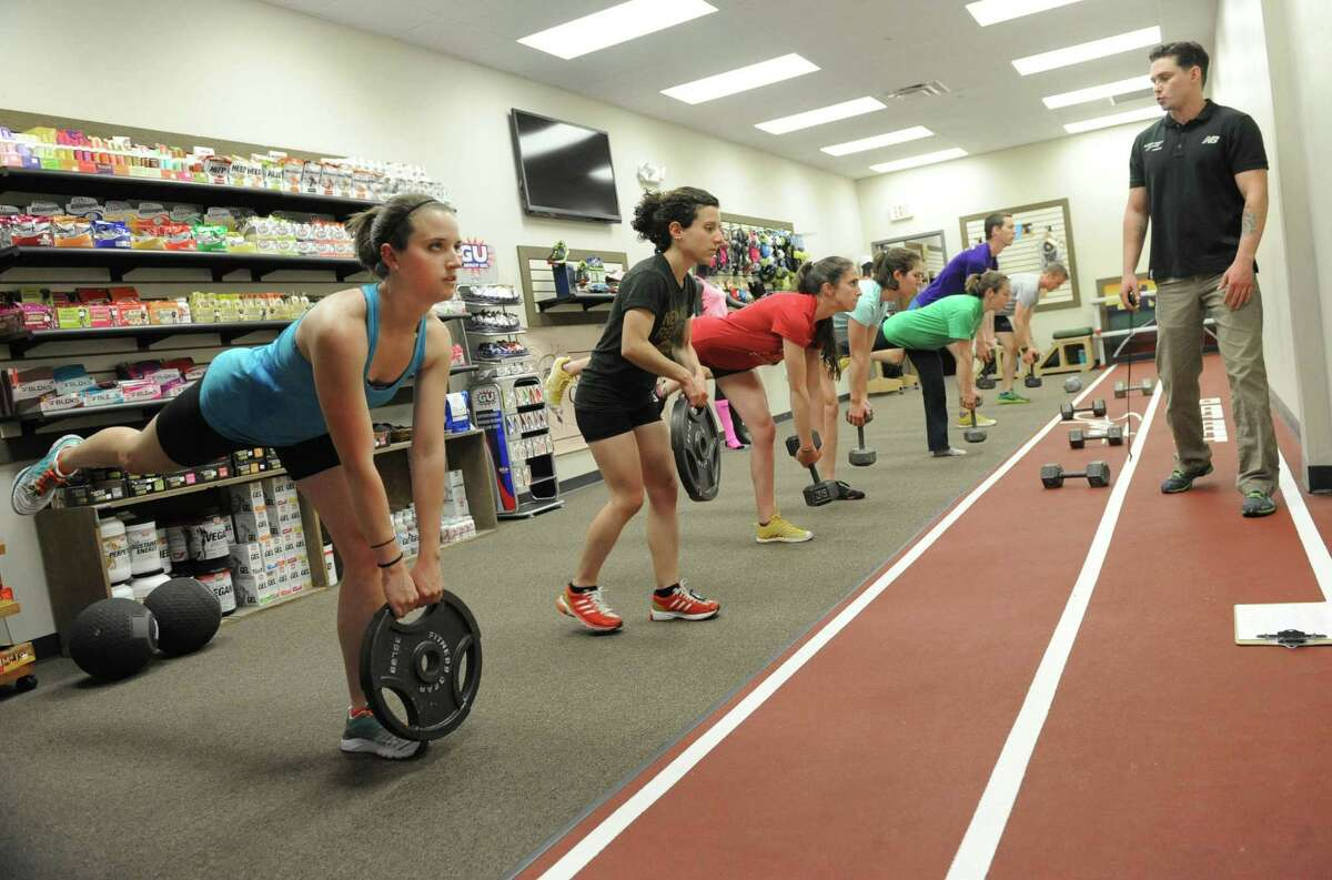 Employees and members of the Fleet Feet team do their twice-weekly strength training session with certified personal trainer Adam Harding, right, at Fleet Feet Sports on Wednesday, May 15, 2013 in Colonie, N.Y. (Lori Van Buren / Times Union)
