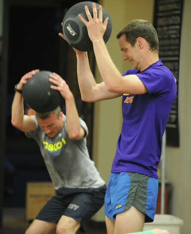Ken Little of Round Lake, left, and Ben Rea of Latham slam medicine balls on the ground as employees and members of the Fleet Feet team do their twice-weekly strength training session at Fleet Feet Sports on Wednesday, May 15, 2013 in Colonie, N.Y. (Lori Van Buren / Times Union) Photo: Lori Van Buren / 00022331A