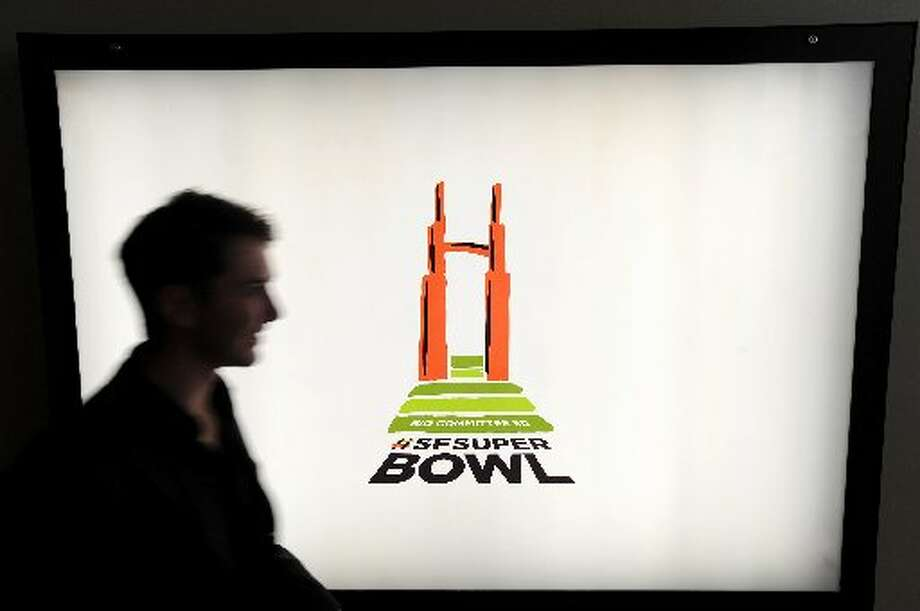 A worker at Goodby, Silverstein & Partners passes a Super Bowl bid logo during the launch of San Francisco's drive to host a Super Bowl on Thursday, Oct. 18, 2012, in San Francisco.