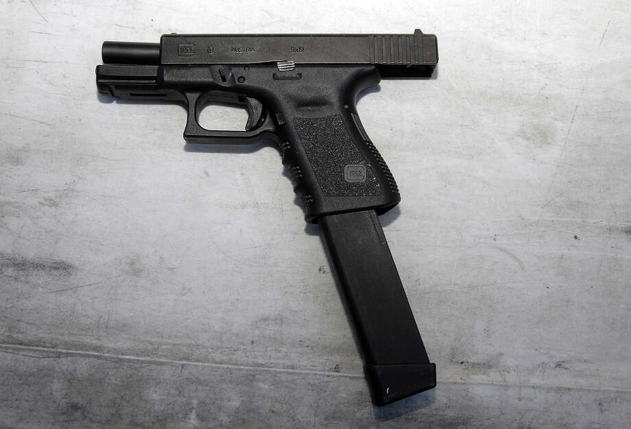 A Glock pistol with extended magazine similar to the one police say was used in a Beacon Hill shooting following a concert there. Prosecutors claim a gunman fired 13 shots from the .40 cal. pistol, one of which narrowly missed a sleeping woman. Photo: AP / Pima County Sheriff