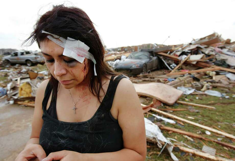 Cindy Wilson texts to friends after her home was destroyed in the afternoon tornado. Cindy and her husband, Staff Sgt. B. Wilson, took cover in their home's bathtub when the tornado hit. Cindy received a deep gash to her forehead and her wound  was treated by first responders at the scene. Tornado caused extensive damage in the Madison Place Addition, near SE 8 and Tower in Moore, on Monday, May 20, 2013.    (AP Photo/ The Oklahoman, Jim Beckel) Photo: Jim Beckel, Associated Press / The Oklahoman