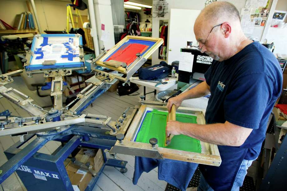 Tom Neville does screen printing at Shirt Works in Stamford, Conn., on Tuesday, May 21, 2013. Photo: Lindsay Perry / Stamford Advocate