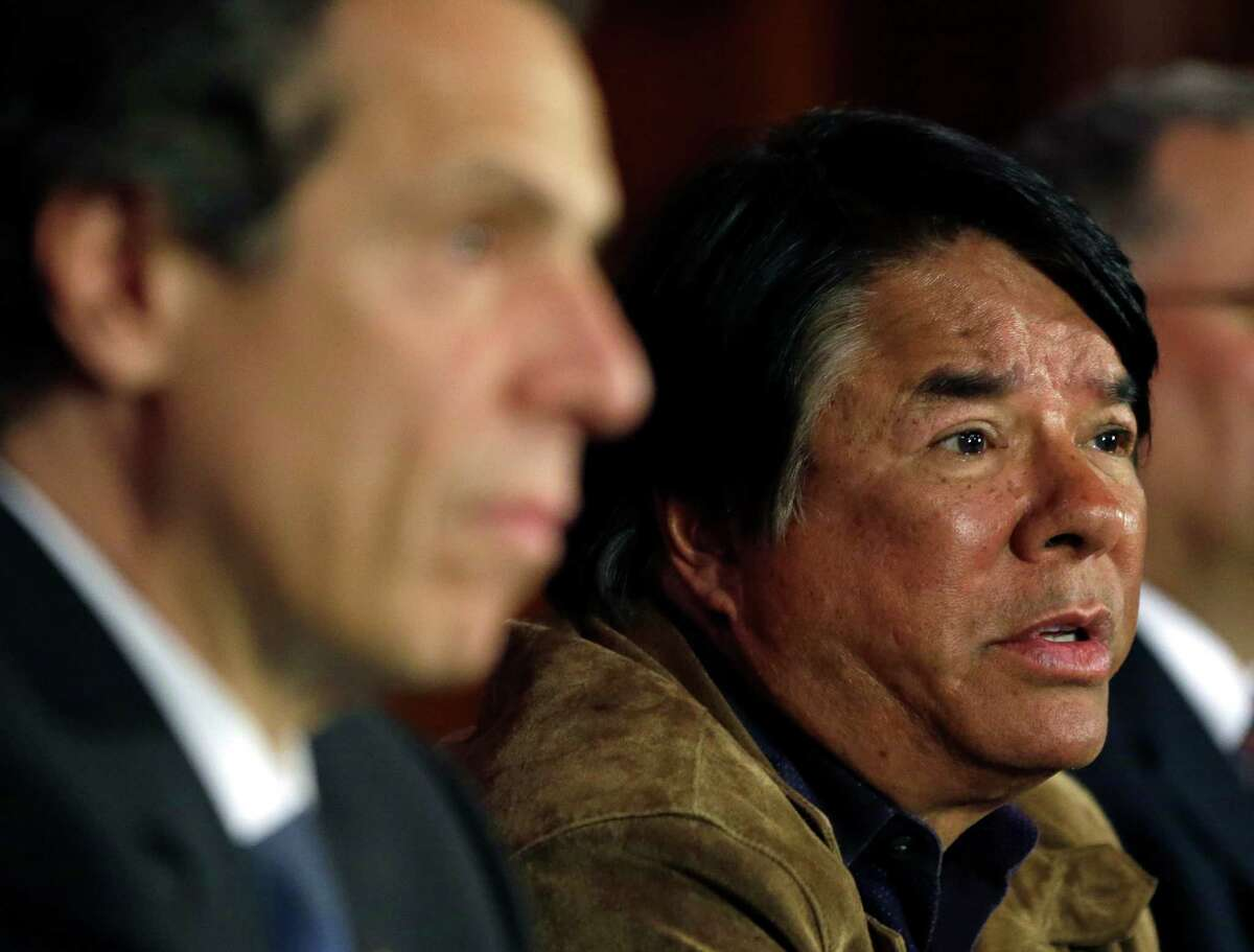 Ray Halbritter of the Oneida Indian Nation speaks during a news conference as New York Gov. Andrew Cuomo, left, listens on Thursday, May 16, 2013, in Albany, N.Y. The Oneidas have struck a deal with the Cuomo administration to guarantee exclusive territory for their central New York casino in exchange for an estimated $50 million in annual payments to the state. The proposed deal would be part of Cuomo's proposal to bring three Las Vegas casinos to upstate New York at yet-to-be-identified locations. (AP Photo/Mike Groll)