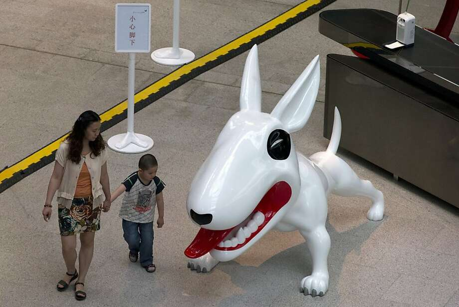 Not quite as imposing as the elephant, but still a little scary:A woman and child walk watch a dog sculpture in Beijing, China. Photo: Ng Han Guan, Associated Press