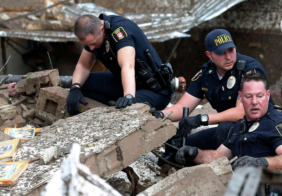 Moore police dig through the rubble of the Plaza Towers Elementary School following a tornado in Moore, Okla., Monday, May 20, 2013. A tornado as much as a mile wide with winds up to 200 mph roared through the Oklahoma City suburbs Monday, flattening entire neighborhoods, setting buildings on fire and landing a direct blow on an elementary school. Photo: Sue Ogrocki, ASSOCIATED PRESS / AP2013