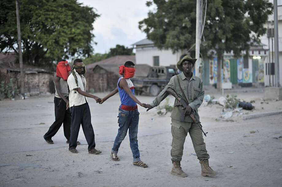 Rounded up: Three young men are led by a member of the Somali Police Force to a holding area with other civilians during a security operation in Mogadishu, Somalia. Police cordoned off a one-square-mile area and temporarily detained young men to determine whether they had any links to an extremist group. Photo: Tobin Jones, AFP/Getty Images