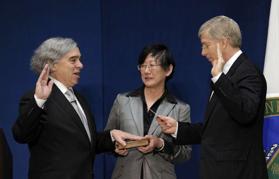 Dr. Ernest Moniz, left,  stands with his wife Naomi, center, as Energy Deputy Secretary Daniel Poneman, right, administers the oath to Moniz who was sworn in as the Secretary of Energy during a ceremony at the Department of Energy in Washington, Tuesday, May 21, 2013. (AP Photo/Susan Walsh) Photo: Associated Press