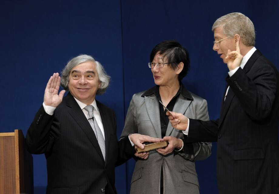 Dr. Ernest Moniz, left, responds to a noise as he stands with his wife Naomi, center, as Deputy Energy Deputy Secretary Daniel Poneman, right, administers the oath of office to Moniz who was sworn in as Energy Secretary of Energy, Tuesday, May 21, 2013, during a ceremony at the Energy Department in Washington. (AP Photo/Susan Walsh) Photo: Associated Press