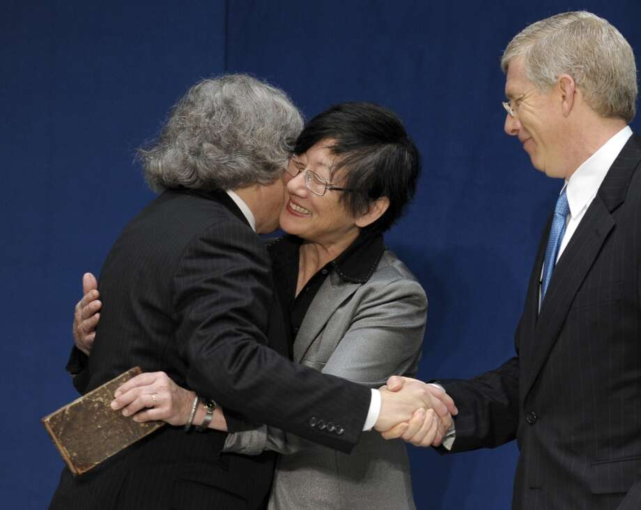 Dr. Ernest Moniz, left, hugs his wife Naomi, center, ad shakes hands with Deputy Energy Deputy Secretary Daniel Poneman, right, after Poneman administered the oath of office to Moniz as Energy Secretary of Energy, Tuesday, May 21, 2013, during a ceremony at the Energy Department in Washington. (AP Photo/Susan Walsh) Photo: Associated Press