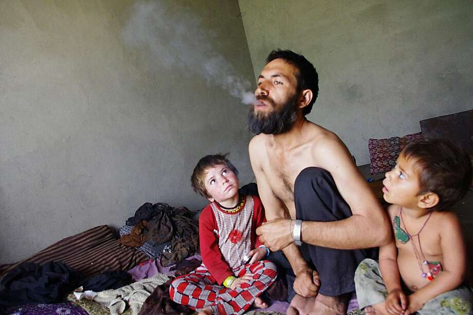Setting a bad example: Afghan drug addict Abdul Rahman exhales after smoking opium as his children watch him at his home in Laghman province. The number of Afghan heroin addicts tripled to 150,000, according to the United Nations, with 230,000 people using opium in 2012. Photo: Waseem Nikzad, AFP/Getty Images