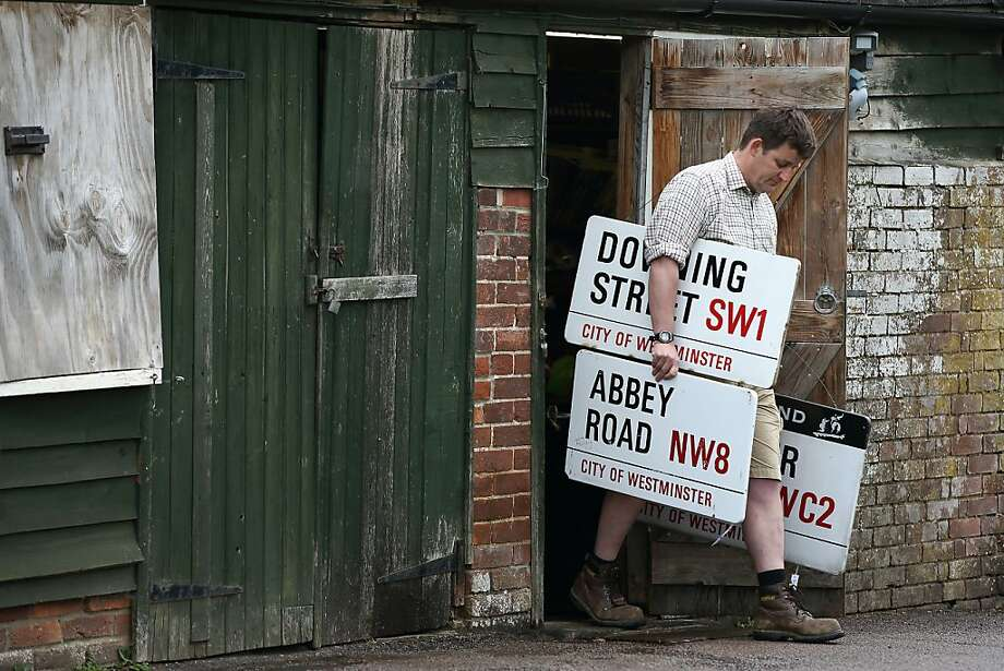 Where's Baker Street? Rupert van der Werff, assistant at Summers Place Auctions Ltd, carries historic London street signs ahead of their sale at auction. Two distinctive enameled street signs, Downing Street and Abbey Road, along with a collection of smaller signs, were sold for a combined 25,000. Photo: Justin Tallis, AFP/Getty Images