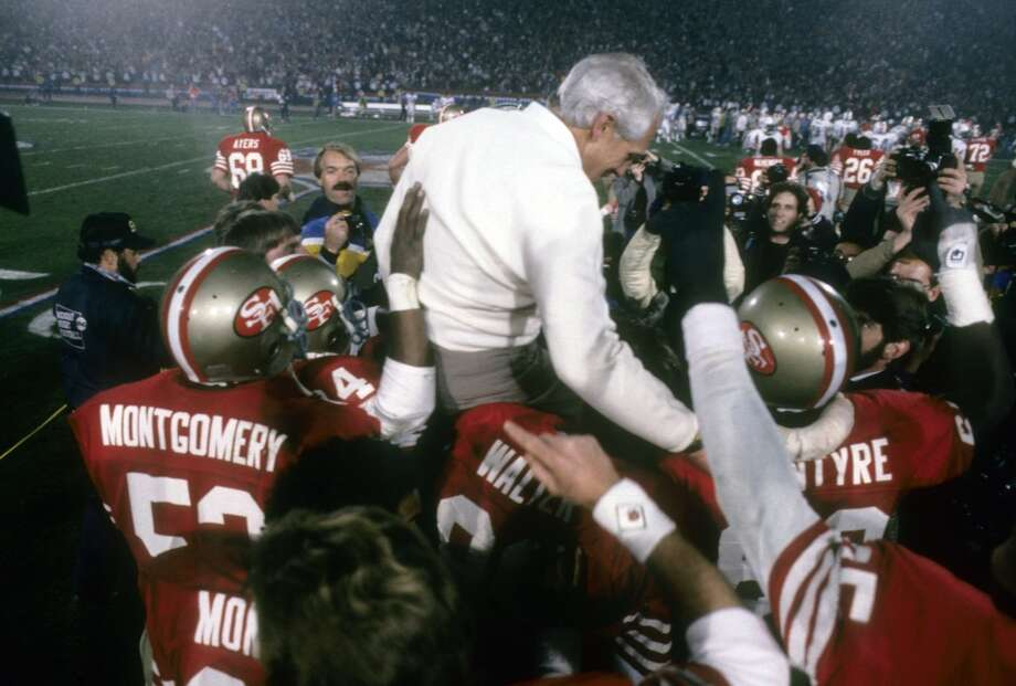Head Coach Bill Walsh of the San Francisco 49ers is carried off the field on the shoulders of two of his players after the 49ers defeated the Miami Dolphins in Super Bowl XIX  on January 20, 1985 at Stanford Stadium in Palo Alto, California.