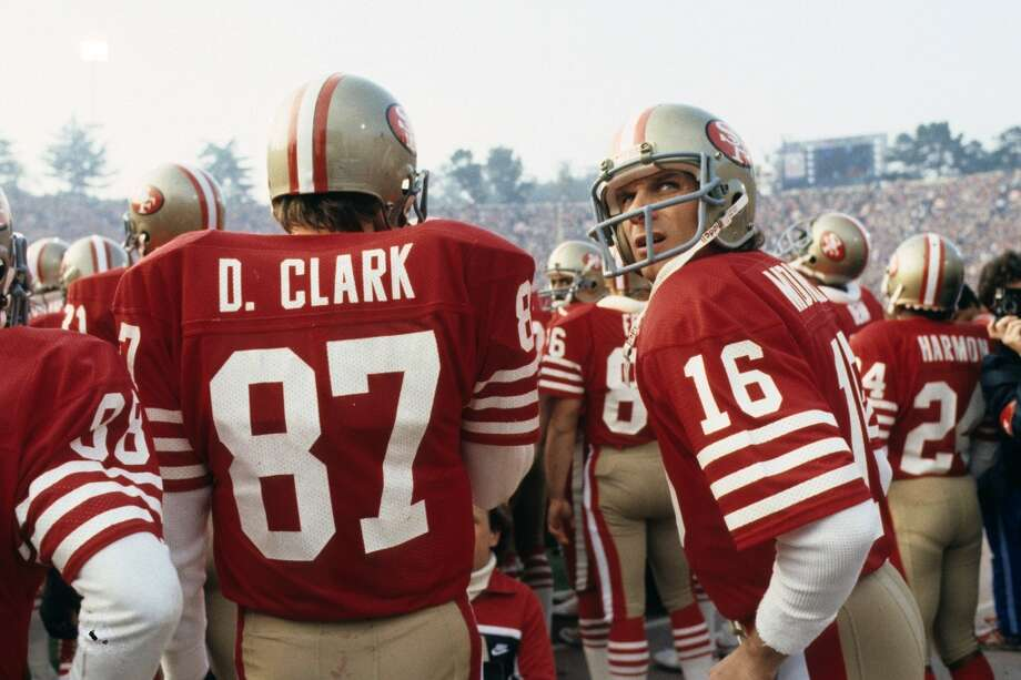 Quarterback Joe Montana of the San Francisco 49ers stands next to receiver Dwight Clark prior to player introductions before the start of Super Bowl XIX at Stanford Stadium on January 20, 1985.