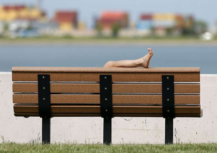 Boston baked: A person with only a leg visible lies on a bench on the beach in the South Boston, where temperatures reached into the 80s.  Photo: Michael Dwyer, Associated Press