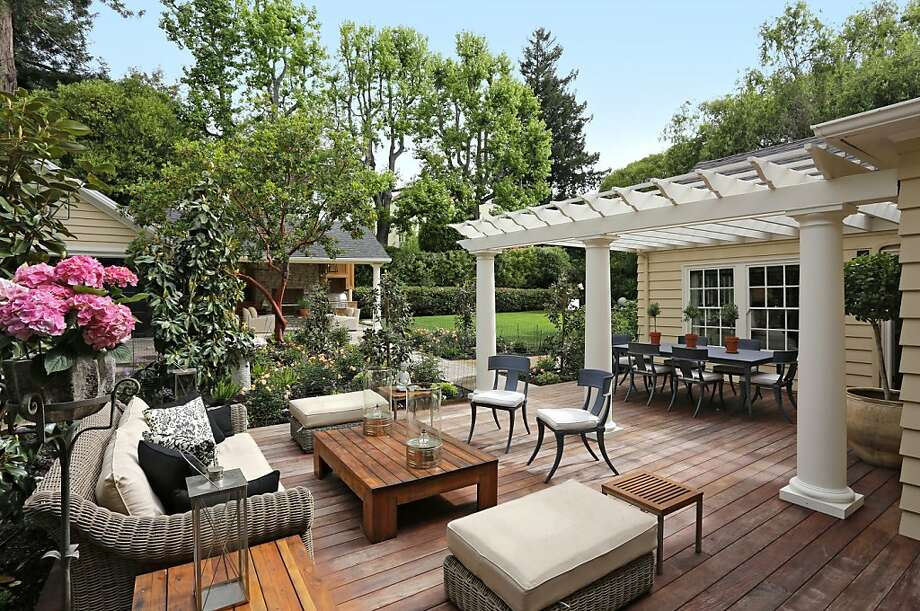 A hardwood deck, along with outdoor fireplace and grill area, make the yard ideal for entertaining. Photo: Liz Rusby/The Grubb Co.