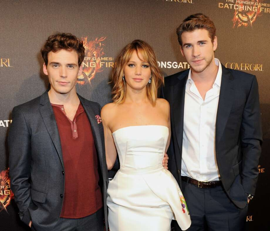 (L to R) Actors Sam Claflin, Jennifer Lawrence and Liam Hemsworth arrive on the Red Carpet at Lionsgate's 'The Hunger Games: Catching Fire' Cannes Party at Baoli Beach sponsored by COVERGIRL on May 18, 2013 in Cannes, France.  (Photo by Dave M. Benett/Getty Images for Lionsgate)