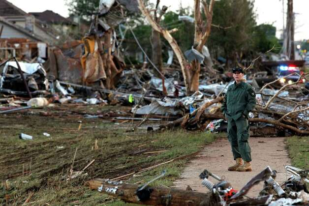 A member of a security team helps guard an area of rubble from a destroyed residential neighborhood, one day after a tornado moved through Moore, Okla., Tuesday, May 21, 2013. The huge tornado roared through the Oklahoma City suburb Monday, flattening entire neighborhoods and destroying an elementary school with a direct blow as children and teachers huddled against the winds. Photo: Brennan Linsley