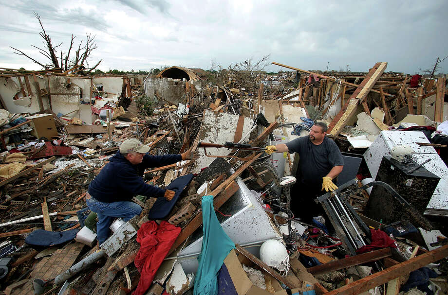 Dalton Sprading, right, hands a gun to his uncle Roger Craft as he salvages items from his tornado-ravaged home Tuesday, May 21, 2013, in Moore, Okla.  A huge tornado roared through the Oklahoma City suburb Monday, flattening an entire neighborhoods and destroying an elementary school with a direct blow as children and teachers huddled against winds. Photo: Charlie Riedel, ASSOCIATED PRESS / AP2013