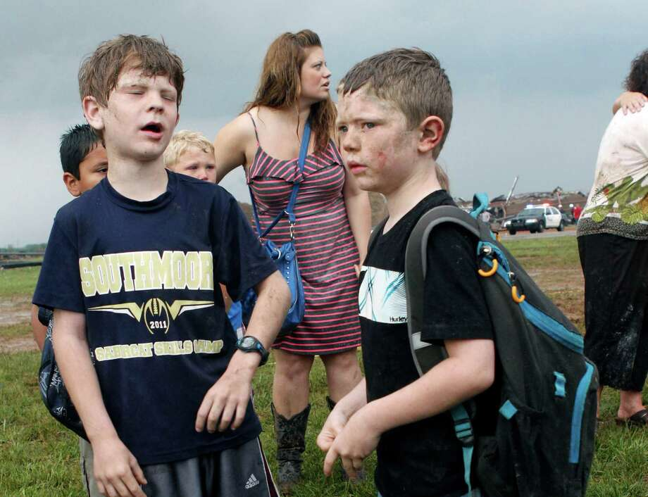 Children wait for their parents to arrive at Briarwood Elementary school after a tornado destroyed the school in south  Oklahoma City, Okla, Monday, May 20, 2013. Near SW 149th and Hudson.  (AP Photo/ The Oklahoman,  Paul Hellstern) Photo: PAUL HELLSTERN, Associated Press / The Oklahoman