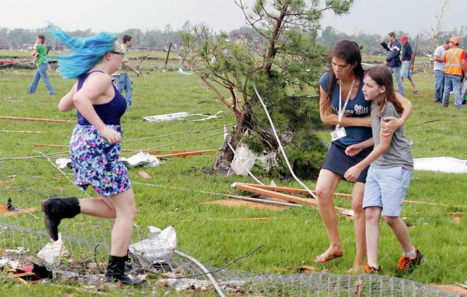 A parent rushes to embrace her child as a teacher escorts her away from Briarwood Elementary school after a tornado destroyed the school in south  Oklahoma City, Okla, Monday, May 20, 2013. Near SW 149th and Hudson. Photo: PAUL HELLSTERN, Associated Press / The Oklahoman