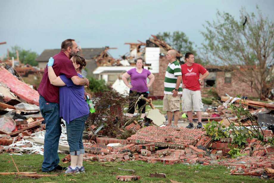 Glenn Rusk hugs his neighbor Sherie Loman outside her home north of Briarwood Elementary School after a tornado moved through the area, in Moore, Okla., Monday, May 20, 2013. Photo: The Oklahoman, David McDaniel