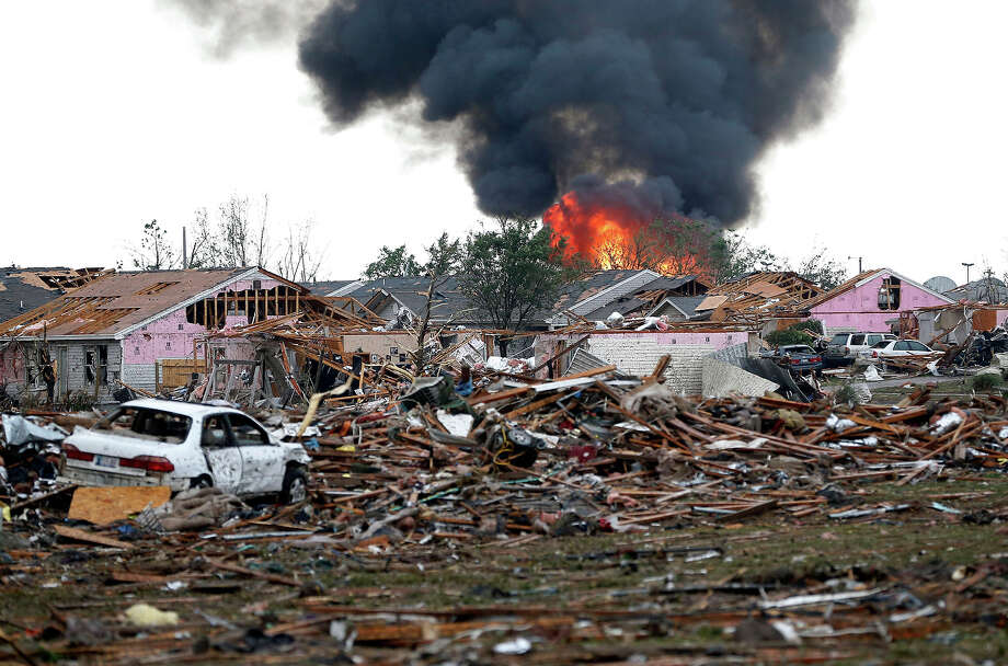 A fire burns in the Tower Plaza Addition in Moore, Okla., following a tornado Monday, May 20, 2013. A tornado as much as a mile wide with winds up to 200 mph roared through the Oklahoma City suburbs Monday, flattening entire neighborhoods, setting buildings on fire and landing a direct blow on an elementary school. Photo: Sue Ogrocki, ASSOCIATED PRESS / AP2013