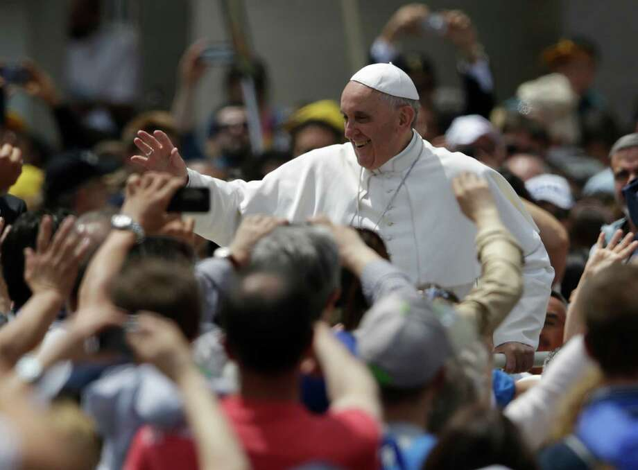 Pope Francis greets the faithful in St. Peter Square at the Vatican, after celebrating a Pentecost mass, Sunday, May 19, 2013. Photo: AP