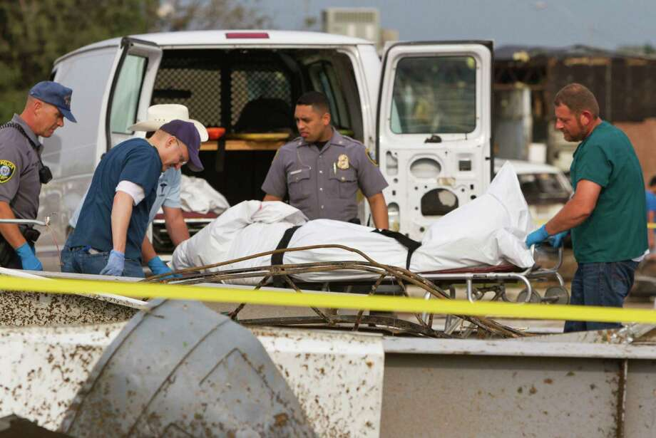 Emergency crews recover a body from the 7-11 store at the corner of Telephone Road and SW 4th Street after a tornado in Moore, Okla. on Monday, May 20, 2013. (AP Photo/Alonzo Adams) Photo: Alonzo Adams, Associated Press / FR159426 AP