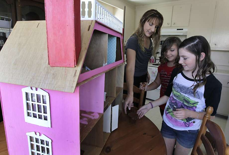 Anne Williams helps daughters Cheyenne (center), 10, and Emily, 12, furnish a dollhouse at their Newark home. The family had to scramble to find a place to live after a landlord kept their security deposit. Photo: Paul Chinn, The Chronicle