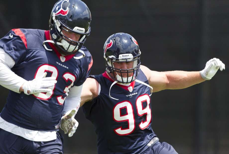 Texans defensive ends Jared Crick (93) and J.J. Watt (99) run through a drill.