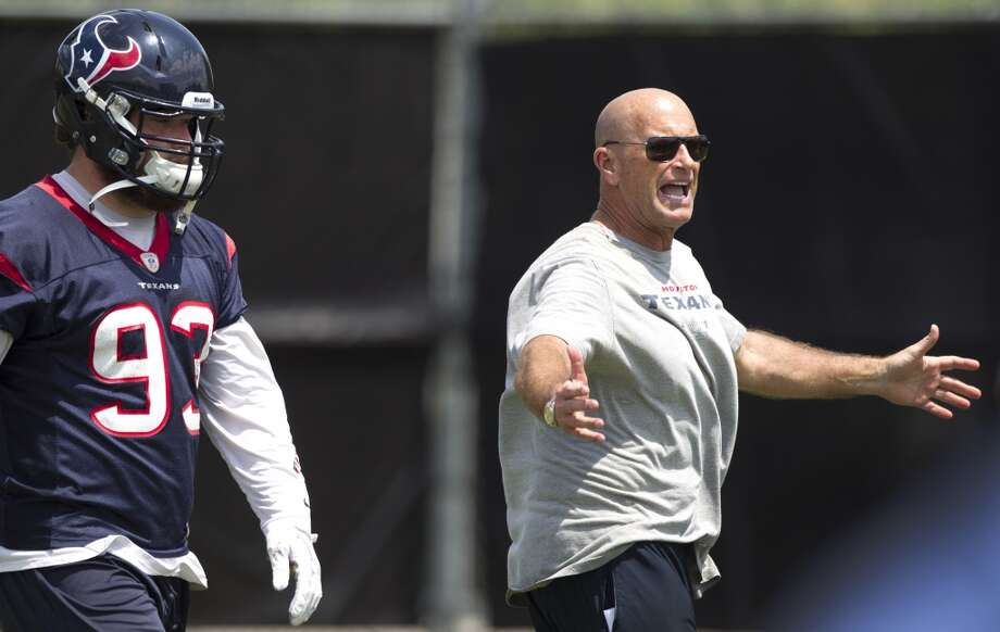 Texans defensive line coach Bill Kollar, right, works with his group as defensive end Jared Crick walks past.