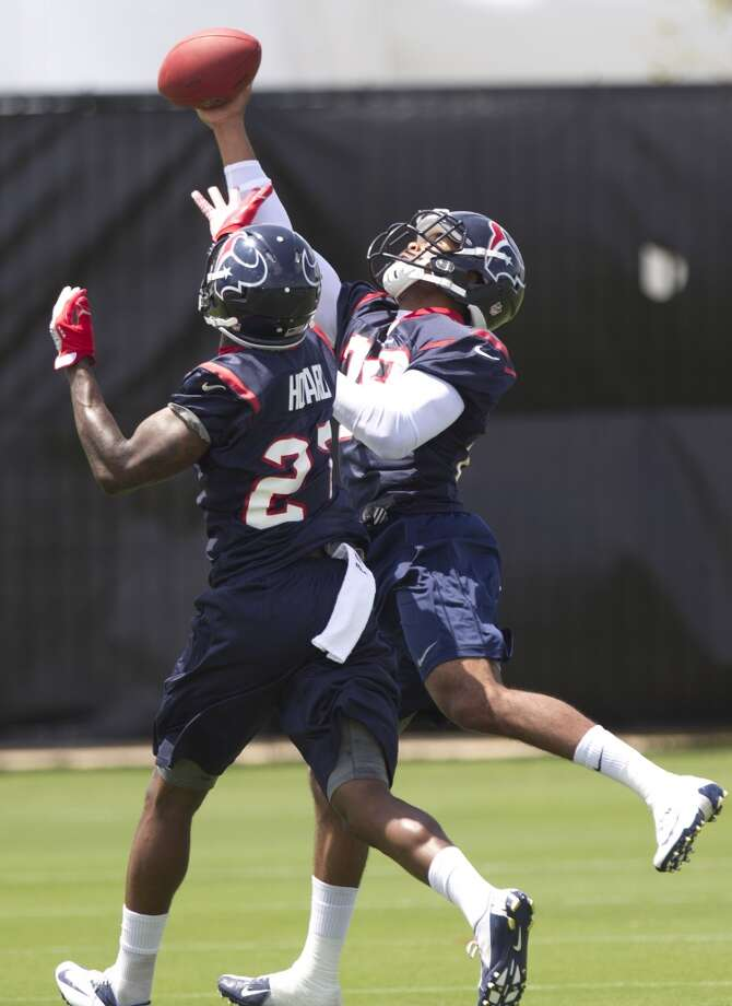 Texans cornerback Travis Howard (27) and safety Jawanza Starling (29) go up for a pass.