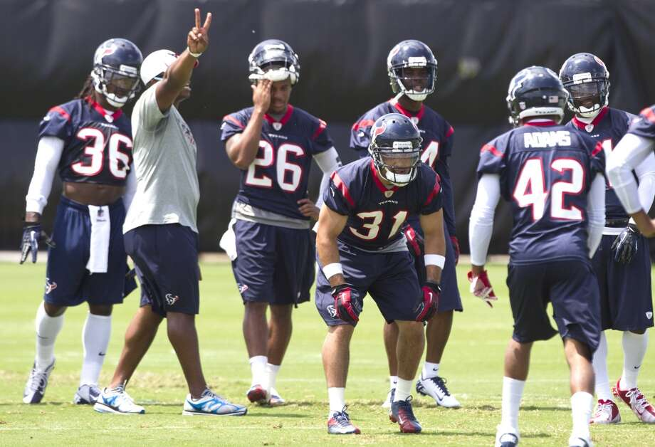 Texans defensive backs coach Vance Joseph calls out a play as safety Shiloh Keo (31) lines up against cornerback Johnny Adamas (42).