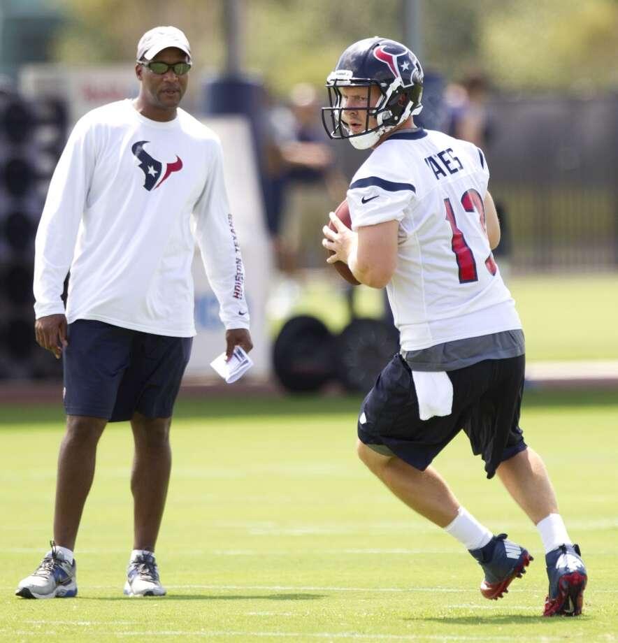 Texans quarterbacks coach Karl Dorrell, left, looks on as quarterback T.J. Yates drops back to pass.