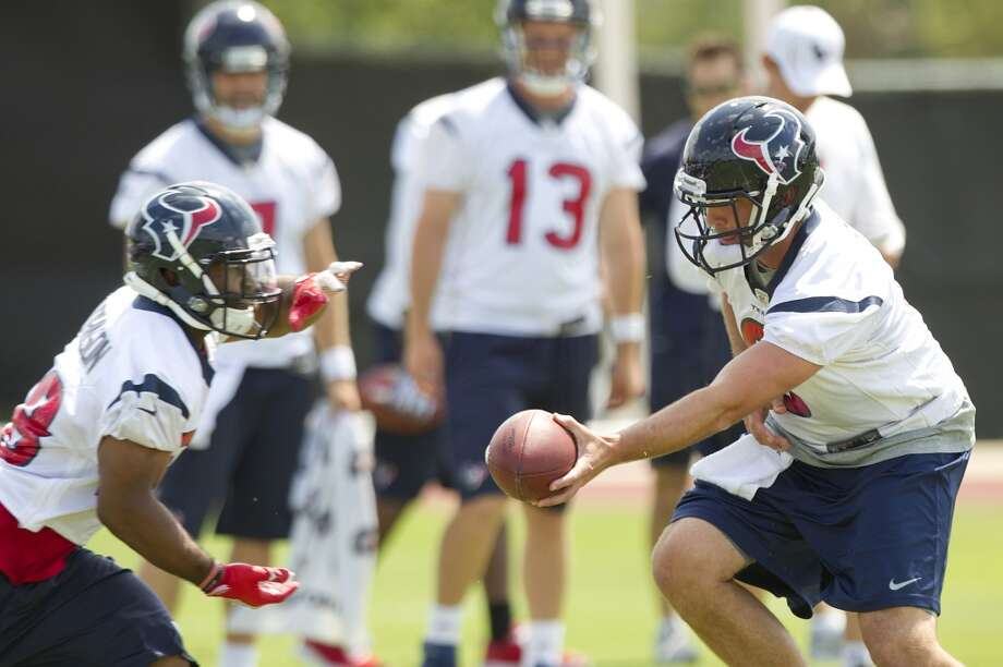 Texans running back Dennis Johnson, left, takes a handoff from quarterback Matt Schaub.