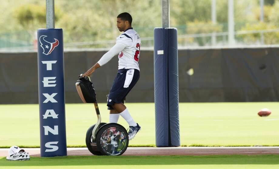 Texans running back Arian Foster parks his Segway as he arrives to practice.