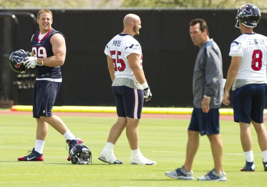 Texans defensive end J.J. Watt (99) walks past center Chris Myers (55), head coach Gary Kubiak and quarterback Matt Schaub at the beginning of practice.