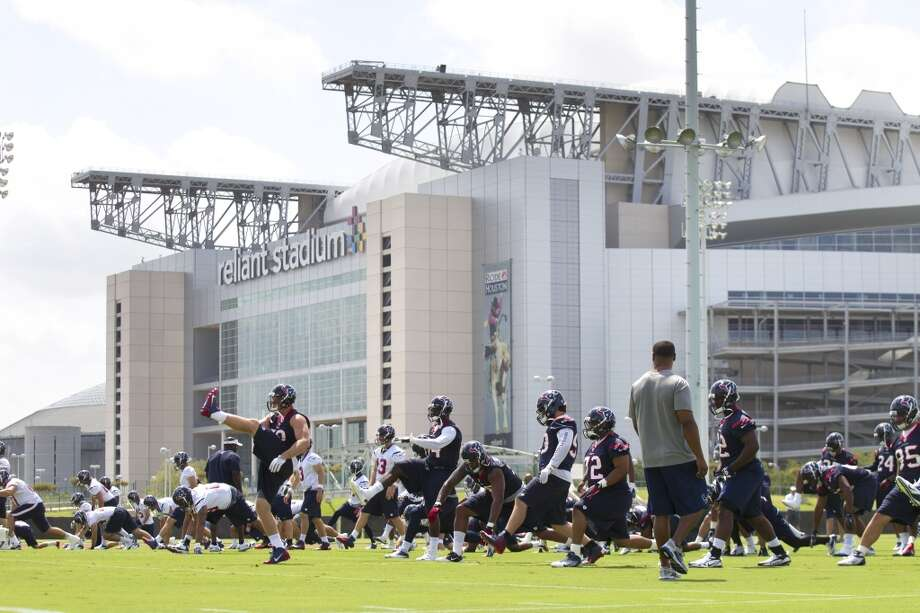 Texans players warm up in the shadow of Reliant Stadium.