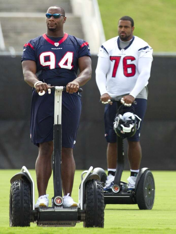 Antonio Smith (94) and Duane Brown (76) arrive at the practice field aboard Segways.